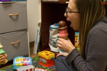 Child and Speech Therapist speaking with ice-cream as microphone.
