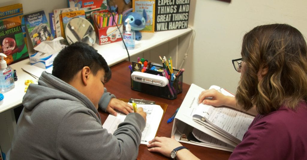 Child writing in speech and language therapy